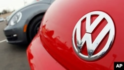 FILE - The Volkswagen logo on the hood of a 2012 Beetle at a Volkswagen dealership. Investigators seized computer hard drives and documents from VW's headquarters in Seoul and from the home of at least one senior manager.