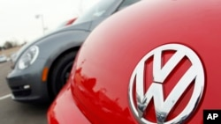 FILE - The Volkswagen logo is seen on the hood of a 2012 Beetle at a Volkswagen dealership in Littleton, Colorado.