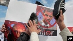 Người Hồi giáo salafist chống chế độ Syria, biểu tình trong thủ đô Beirut của Lebanon dùng giày đập lên hình của Tổng thống Syria al Assad (phải) và hình của Thủ trướng Nga Vladimir Putin