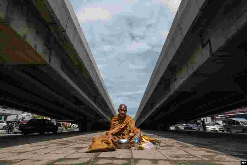A Buddhist monk sits on the ground in between two vehicular overpasses as he waits to receive alms in northern Bangkok.