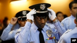 "FILE - An LAPD Cadet Commander adjusts his hat before the LAPD Cadet Program Graduation of the cadet ""Class of 7-2014""."