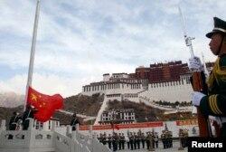 拉萨布达拉宫前面举行升旗典礼,中国武警有人持枪,有人敬礼。(2010年3月28日)