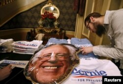 FILE - A vendor looks for a t-shirt size at a U.S. Democratic presidential candidate Bernie Sanders' campaign event in Sioux City, Iowa, United States, Jan. 19, 2016.