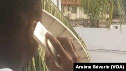 Un usager de téléphonie mobile à Brazzaville, en République du Congo, le 22 juillet 2019. (VOA/Arsène Séverin)