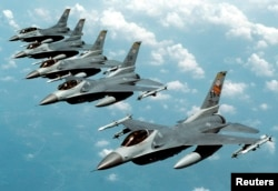 """FILE- Five U.S. Air Force F-16 """"Fighting Falcon"""" jets fly in echelon formation over the U.S. en route to an exercise in this undated photograph."""