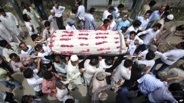 Family members carry the casket of Waja Ahmad Karim Dad, 60, who was killed during a shootout by unidentified men a day earlier, for his burial in Karachi August 18, 2011.