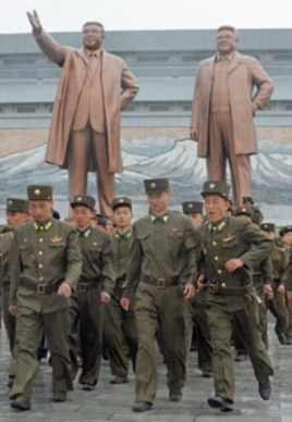 North Korean soldiers walk past bronze statues of North Korea founder Kim Il-sung (L) and late leader Kim Jong-il in Pyongyang, April 25, 2012.