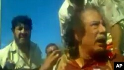 Image taken from amateur video posted on a social media website and obtained by Reuters, October 21, 2011, shows former Libyan leader Moammar Gadhafi, covered in blood, after his capture by NTC fighters in Sirte.