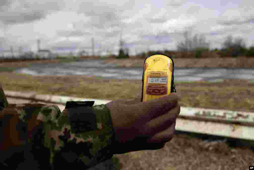 A tour guide measures radiation at the site of Chernobyl. (VOA Photo/D. Markosian)