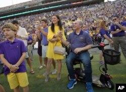 El jefe de la mayoría republicana en la Cámara de Representantes, Steve Scalice, de Luisiana, acompañado de su esposa Jennifer, recibe un homenaje durante un juego de fútbol americano entre la Universidad de Luisiana y el equipo de Troy en Baton Rouge. Sept.30, 2017.