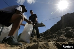 """Члени пожежного відділу Нового Орлеана наповнюють мішки з піском під час підготовки до урагану """"Нейт"""" в Новому Орлеані, 6 жовтня 2017 року."""