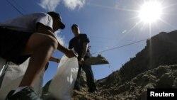 Članovi vatrogasne službe Nju Orleansa pune vreće sa peskom pripremajući se za uragan Nejt.
