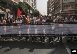 Demonstrators carry a banner with the names of detained activists during a protest in Casablanca, Morocco, Oct. 8, 2017.