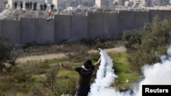 A Palestinian stone-throwing protester uses a sling to throw back a tear gas canister fired by Israeli security officers (rear) during clashes in the West Bank village of Bilin near Ramallah, January 4, 2013.