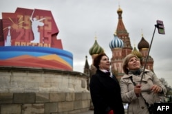 Women pose for a selfie in front of the historical Place of Execution decorated with a banner for the upcoming Victory Day celebrations on the Red Square in central Moscow, April 30, 2015.
