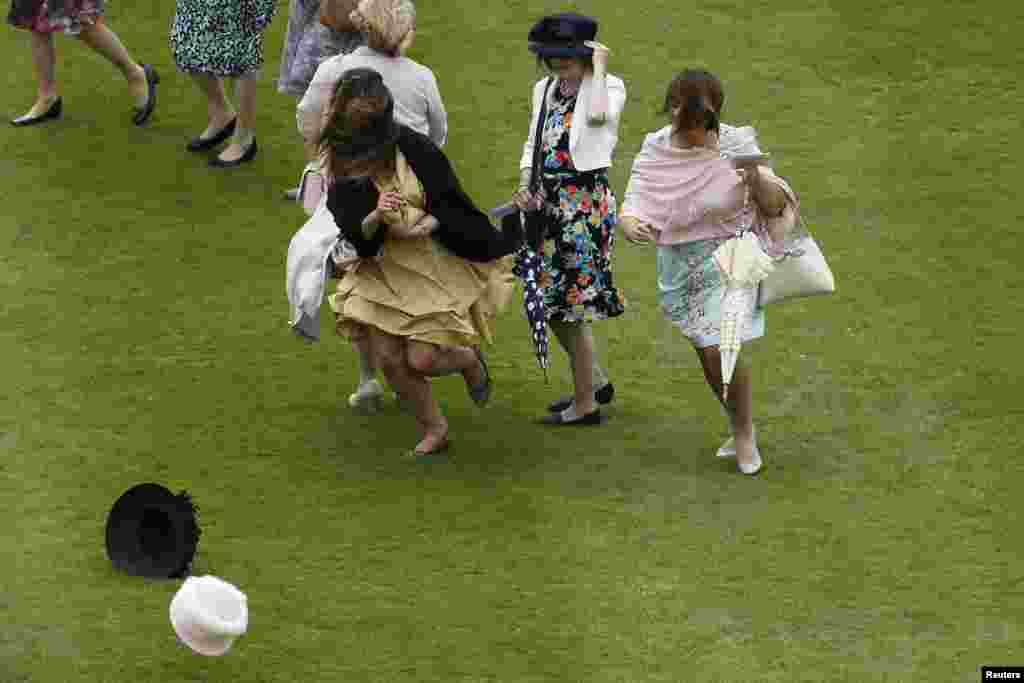 Ladies run after their hats blown by strong winds at a garden party at Buckingham Palace in central London, Britain.
