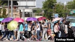 올들어 처음 폭염주의보가 내려진 서울에서 20일 경복궁 앞을 지나는 시민들이 양산과 옷을 뒤집어 쓴 채 걸어가고 있다.