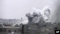 This image made from amateur video released by Ugarit News and accessed June 17, 2012, purports to show smoke rising from buildings in Rastan town, in Homs province, Syria.