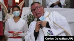 """Sergio Valverde Espinoza, a Catholic priest of the Cristo Rey church who modified a popular song called """"Sopa de Caracol,"""" or Snail Soup in English, gestures during a Mass in San Jose, Costa Rica, Sunday, May 2, 2021."""