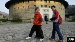 រូបភាពឯកសារ៖ សិស្សសាលាដើរកាត់ផ្ទះរាលមូលដ៏ចាស់មួយដែលជាផ្ទះបុរាណរបស់ក្រុមជនជាតិចិនភាគតិច Hakka ក្នុងភូមិ Yongding ខេត្ត Fujian កាលពីថ្ងៃទី១៥ ខែធ្នូ ឆ្នាំ២០០៥។