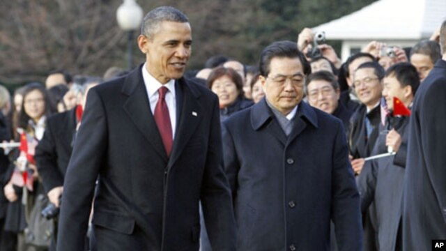 U.S. President Barack Obama and Chinese President Hu Jintao walk past guests during an official South Lawn arrival ceremony for Hu at the White House in Washington, 19 Jan 2011
