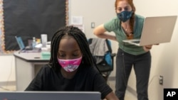 In this Tuesday, Sept. 29, 2020, photo English Language Arts teacher Rebecca Ain, right, helps a student in her class at The Social Justice Public Charter School, in Washington. (AP Photo/Jacquelyn Martin)