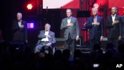 Former Presidents from right, Barack Obama, Bill Clinton, George W. Bush, George H.W. Bush and Jimmy Carter place their hands on their heart for the national anthem at the opening of a hurricanes relief concert in College Station, Texas, Oct. 21, 2017.