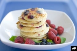 A plate of pancakes made with blueberries and granola with raspberries on the sides. (File Photo)