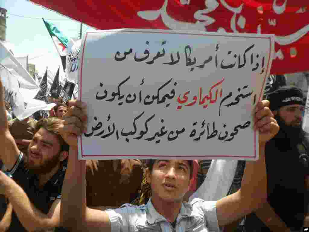 """This image provided by ENN shows a protester with a sign reading """"If America does not know who used the chemical weapons, so it could be flying saucers from another planet,"""" Sarmada, Idlib, Syria, May 3, 2013."""