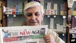 A fish-and-chips shop owner holds a copy of the New Age Newspaper which debuted Monday 06 Dec 2010 in Johannesburg with denials it is an agent of the governing African National Congress, (ANC)