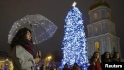 一名乌克兰妇女在首都基辅市中心打着伞站在一棵圣诞树下。(2017年12月20日)
