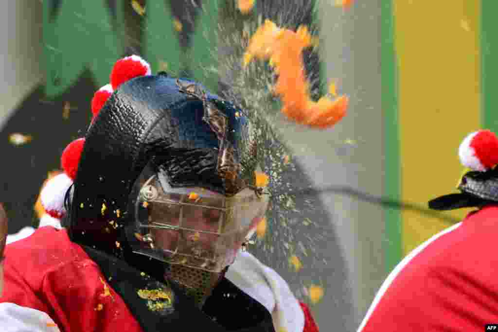 "Men with helmets are hit by oranges during the traditional ""battle of the oranges"" held during the carnival in Ivrea, near Turin, Italy."