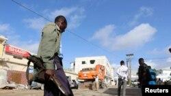 Un soldat somalien gardent les corps des victimes de l'attaque à la voiture piégée revendiquée par les shebab près de l'hôtel Nasahablood à Mogadiscio en Somalie, le 26 juin 2016.