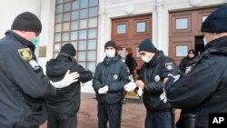 Policiers ukrainiens avant une opération de sécurisation près de l'aéroport de Kharkiv après l'évacuation de plus de 70 personnes de Chine en raison de l'épidémie de COVID-19, le 20 février 2020, (Photo AP/Igor Chekachkov)