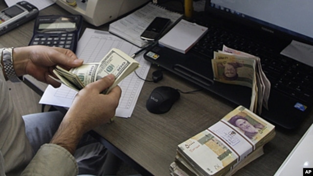 A currency exchange bureau worker counts US dollars, as Iranian bank notes are seen at right with portrait of late revolutionary founder Ayatollah Khomeini, in downtown Tehran,  December 21, 2011.