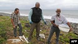 Un expert malais, au centre, examine des fragements de l'avion de Malyasia Airlines qui assurait le vol MH370 sur une plage à Saint-Andre de la Reunion,4 aout 2015.