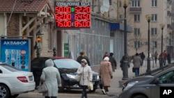 Una pantalla muestra las tasas de cambio del rublo en una calle del centro de Moscú. Las expectativas economómicas para el próximo año no lucen bien.