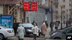 FILE - People walk past a currency exchange rate display in central Moscow, Dec. 1, 2014.