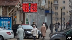People walk past a currency exchange rate display in central Moscow, Dec. 1, 2014.