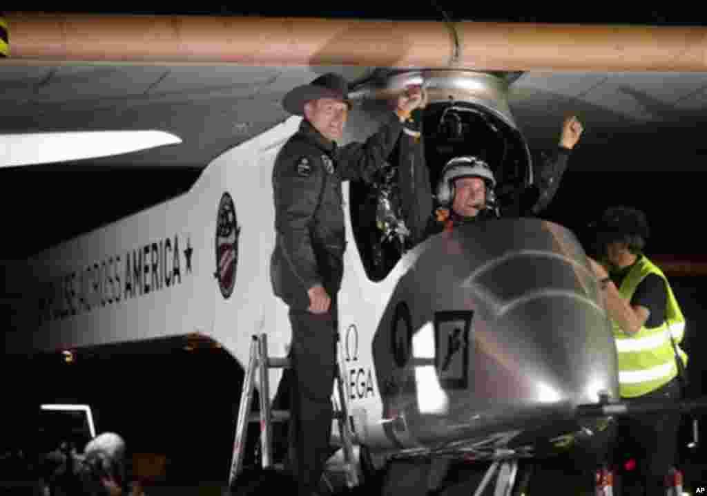 """Solda """"Solar Impulse""""un həmtəsisçisi, pilotu və sahibi Andre Borşberq pilot Bertrand Pikkardı Feniksdəki """"Sky Harbor"""" beynəlxalq hava limanında salamlayır. Mayın 4-ü, 2013-cü il"""