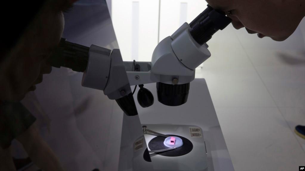 在北京第21届国际科技产业博览会上有人在通过显微镜看电脑晶片 (2018年5月17日)(photo:VOA)