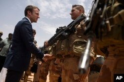 FILE - French President Emmanuel Macron, visits soldiers of Operation Barkhane, France's largest overseas military operation, in Gao, Northern Mali, May 19, 2017.