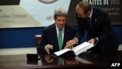 U.S. Secretary of State John Kerry signs the U.N. Arms Trade Treaty at U.N. headquarters in New York City September 25, 2013. Standing beside him is U.N. Under Secretary General for Legal Affairs Miguel de Serpa Soares.