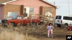 FILE - A young Lakota girl rides her bike on Pine Ridge Indian Reservation, Jan. 10, 2006. At least 60 percent of Pine Ridge homes are substandard, lacking electricity, running water or sewage systems.