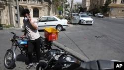 El repartidor de comestibles Saeed Vatanparast, con una máscara facial protectora para ayudar a prevenir la propagación del coronavirus, habla por su teléfono celular frente a una tienda en Teherán, Irán, el martes 21 de abril de 2020.