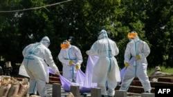 ရန္ကုန္ၿမိဳ႕တြင္ ကိုဗစ္ေၾကာင့္ေသဆံုးသူတစ္ဦးကို သၿဂိဳၤဟ္ၿပီး ေတြ႔ရသည့္ PPE ဝတ္စံုဝတ္ ပရဟိတလုပ္သားမ်ား။ (ႏိုဝင္ဘာ ၂၅၊ ၂၀၂၀)