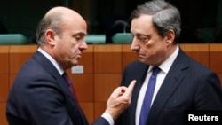 Spain's Economy Minister Luis de Guindos talks to European Central Bank (ECB) President Mario Draghi (R) during a eurozone finance ministers meeting in Brussels, Dec. 17, 2013.