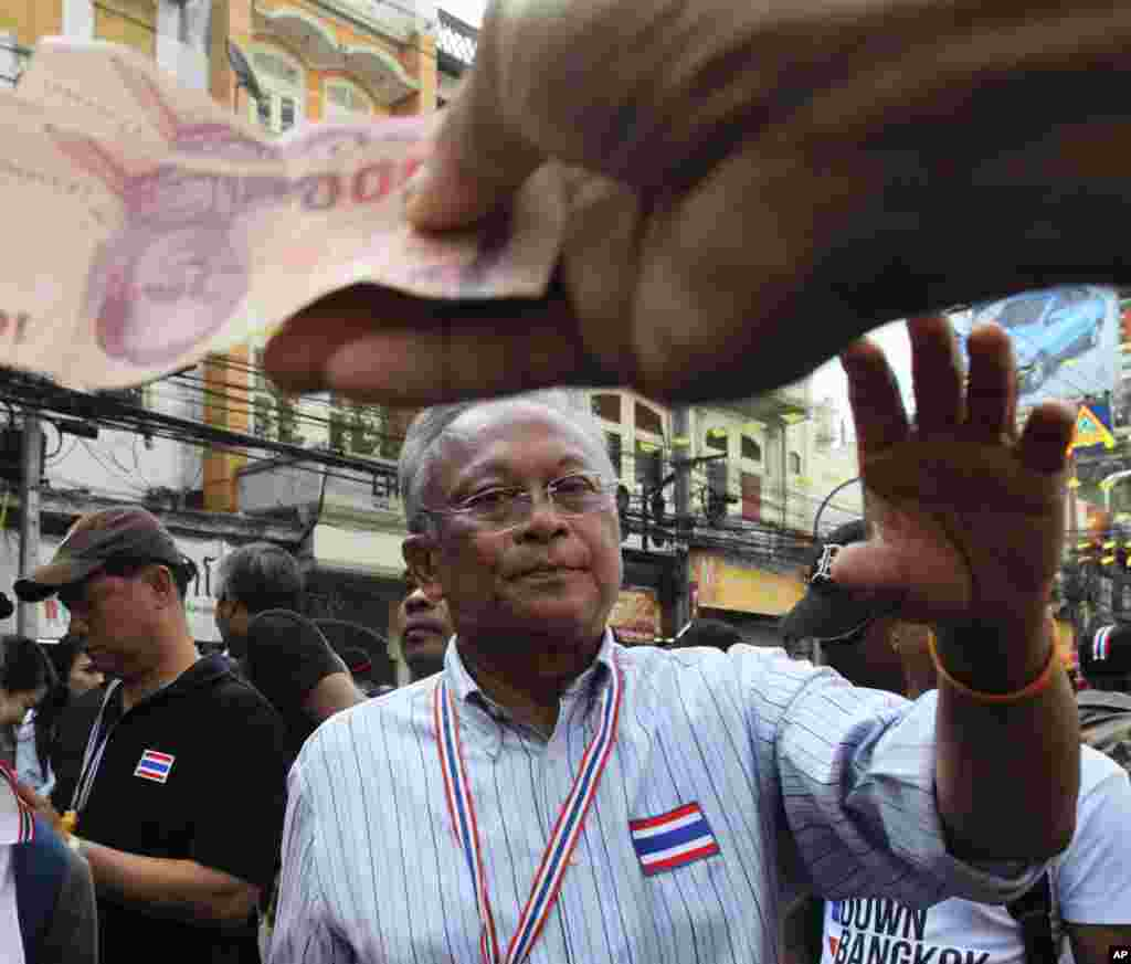 Anti-government protest leader Suthep Thaugsuban collects donations from supporters during a march through streets in Bangkok, Feb. 7, 2014.