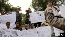 FILE - A Sept. 2014 photo shows protesters holding posters during a rally against the Islamic State group, in Jakarta, Indonesia.