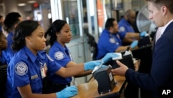 Transportation Security Administration employees check passengers' identifications at a security checkpoint at LaGuardia Airport in New York, Thursday, May 26, 2016. (AP Photo/Seth Wenig)